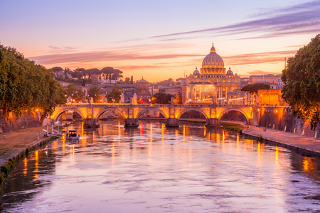 Skyline of Rome in a magenta twilight with San Pietro basilica, at SantAngelo bridge and Tevere river illuminated by city lights of Roma in Italy Stock Photo