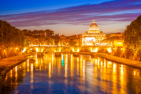 Rome skyline at night with San Pietro basilica or Saint Peter cathedral with SantAngelo bridge reflected on Tevere river illuminated by city lights of Roma in Italy.