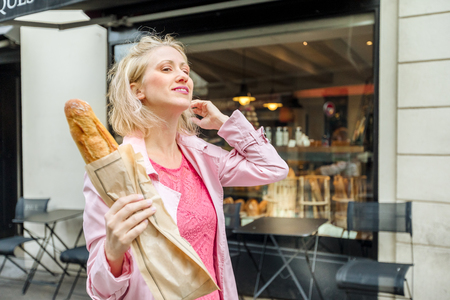 Cheerful elegant woman holding baguette in rue Lepic in Montmartre, Paris, France. Caucasian blonde businesswoman with traditional French bread outdoor. Bakery on blurred background.