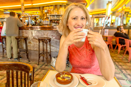 Happy elegant beauty woman drinking capuccino with French brulee creams. Travel lifestyle female in popular cafe-brasserie of Montmartre, Paris. Caucasian blonde businesswoman enjoying her breakfast.