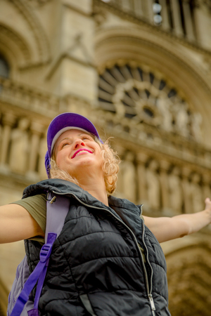 Close up of happy woman with open arms at Notre Dame Cathedral