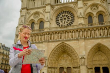 Travel France tourist woman in Paris looking at subway map outdoors