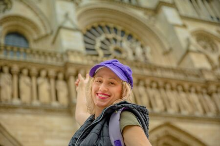 Happy young tourist caucasian woman pointing Notre Dame Cathedral on blurred background