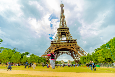 Tourist woman jumping at Tour Eiffel, icon of Paris. Caucasian lifestyle traveler enjoing at Eiffel Tower from Champ de Mars garden in Paris, France. Freedom and travel concept in European Capitals.