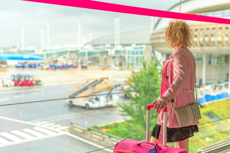 Businesswoman in airport looking through the window at planes. Traveler elegant caucasian woman standing with luggage watching at airport window. Blurred background with copy space. Travel lifestyle. Stock Photo