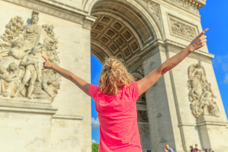 Happy woman with open arms at Arch of triumph. Caucasian lifestyle traveler enjoys at Arc de Triomphe in Paris, France. Holidays in European Capitals. Freedom and travel concept. Blurred background. Stock Photo