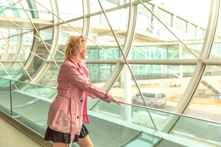 Businesswoman in airport looking through the window waiting for flight. Traveler elegant caucasian woman standing watching at airport window. Travel lifestyle. Business travel concept Stock Photo
