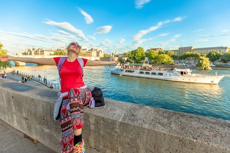 Traveler freedom concept. Caucasian lifestyle woman with open arms enjoying the Seine. Bateau-mouche and Pont Neuf on a blurred background. Tourist traveler and popular landmarks of Paris, France.