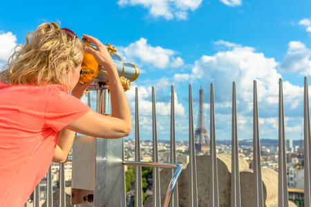 Caucasian lifestyle traveler looking skyline of Paris with tourist binocular from top of Arc de Triomphe. Blonde tourist woman looking Tour Eiffel. Landmark in Paris, France, Europe. Stock Photo