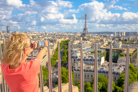 Paris skyline aerial view. Caucasian lifestyle traveler taking picture with smartphone from top of Arc de Triomphe. Blonde tourist woman takes shot of Tour Eiffel. Landmark in Paris, France, Europe.
