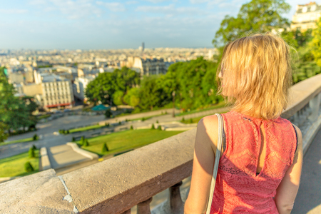 Close up of elegant caucasian woman looking skyline of Paris from Sacred Heart viewpoint. Parisian views from terrace of Sacre Coeur Cathedral, the highest city point of Paris, France. Sunny day. Stock Photo