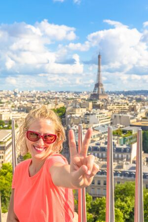 Caucasian lifestyle traveler woman at top of Arc de Triomphe. Tour Eiffel and Paris skyline on blurred background