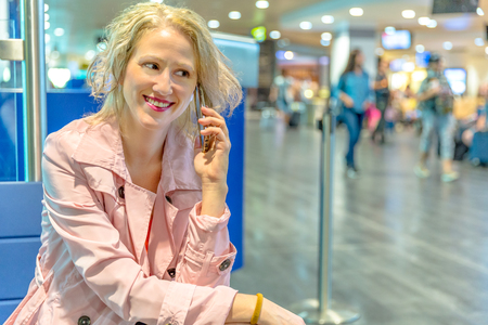 Businesswoman at boarding gate, sitting talking on smartphone. Woman using mobile phone app for conversation. Female enjoing in airport while waiting to get on air flight.Blurred background.Copy space