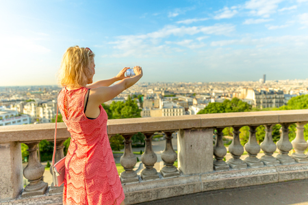Elegant caucasian woman taking picture with smartphone from Sacred Heart viewpoint. Parisian views from terrace of Sacre Coeur Cathedral, the highest city point of Paris, France. Sunny day. Stock Photo