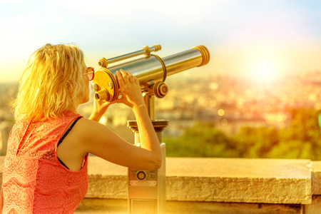 Close up of elegant caucasian woman looking skyline of Paris with tourist binocular from Sacred Heart viewpoint. Parisian views from terrace of Sacre Coeur Cathedral, Paris, France. Sunrise light shot Stock Photo