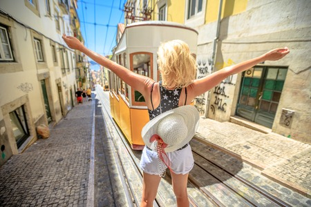 Happy woman with open arms in Lisbon, Portugal, Europe. Blonde caucasian female enjoying in front of Bica Funicular. Elevador or Ascensor da Bica is a popular tourist attraction. Yellow vintage tram.