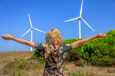 A blond caucasian woman with open arms enjoying in front of wind turbines rotating in Sagres, Algarve, Portugal. Alternative energy, renewable energy and environmental sustainability concept. Stock Photo
