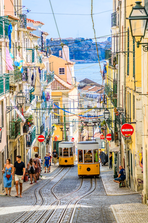 Lisbon, Portugal - August 26, 2017: intersection point of two Bica Funicular. The Elevador or Ascensor da Bica is a popular tourist attraction in Chiado District, Lisbon. Tagus river on background. Editorial