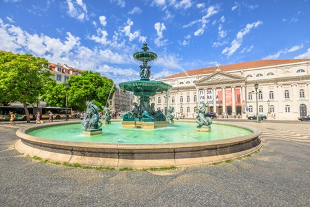 Lisbon, Portugal - August 26, 2017: baroque fountain on popular Praca Dom Pedro IV or Rossio Square in Lisbon downtown, Portugal, Europe. The National Theater D. Maria on background. Sunny day.