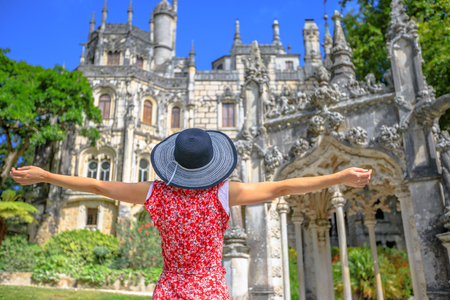 Carefree caucasian woman with open arms looking popular landmark in Sintra, Portugal. Female tourist enjoying in a sunny day. Architecture on blurred background.