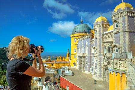 여행 여자 사진 작가는 페냐 국립 궁전 (Pena National Palace) 사진을 찍습니다. 전문 카메라로 사진 작가 Sintra, 포르투갈에서 가장 방문 된 매력의 총을 걸립니다. 유럽 여행 및 관광
