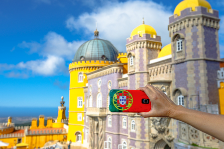 Woman takes photo of Pena National Palace by mobile phone with Portugal flag cover. Tourism and travel in Portugal. Pena Castle is a Unesco Heritage and most visited attraction of Sintra, near Lisbon.