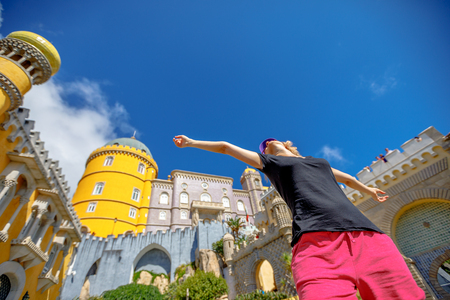 Bottom view of happy woman with open arms at Pena Palace in sunny day. Pena Castle is a Unesco Heritage and one of Seven Wonders of Portugal. Female tourist enjoys of most visited attraction of Sintra Stock Photo