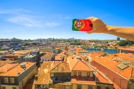 Woman takes photo of Oporto skyline from Miradouro da Vitoria by mobile phone with Portugal flag cover. Dom Luis I on Douro River on blurred background. Tourism and travel in Portugal.