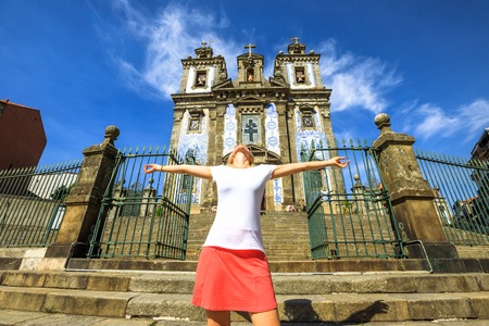 Carefree woman with open arms at Saint Ildefonso church facade. The Igreja de Santo Ildefonso is famous for azulejos and two bells tower. Female tourist enjoying in a sunny day. Oporto, Portugal. Stock Photo