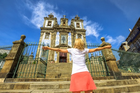 Happy woman with open arms in front of azulejo facade of Saint Ildefonso church. The Igreja de Santo Ildefonso is an eighteenth-century church. Female tourist enjoying in Porto, Portugal. Sunny day. Stock Photo