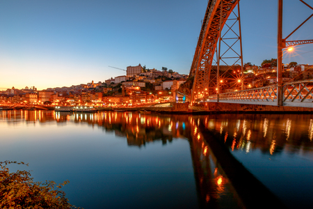 Iconic symbol of Oporto city. Bottom view of scenic iron arch bridge Dom Luis I reflecting on Douro River at twilight in Porto, Portugals second largest city. Picturesque urban evening skyline.