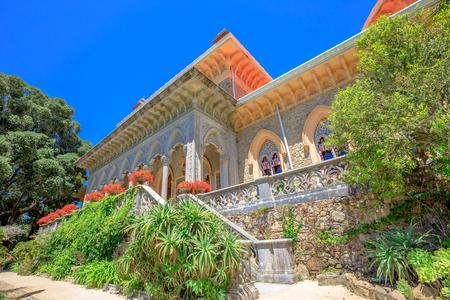 residential: Sintra, Lisbon, Portugal. The arabesque facade of Monserrate Palace surrounded by botanical garden in beautiful sunny day. Palacio de Monserrate is the summer resort of the Portuguese court. Stock Photo