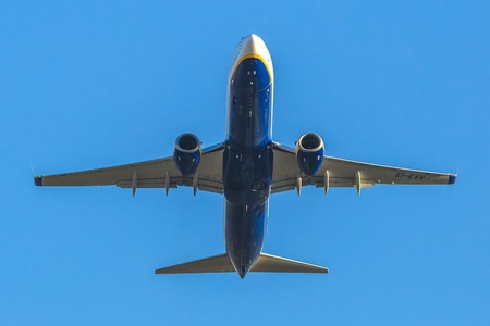 Bologna, Italy - December 20, 2016: Ryanair passenger airplane flying isolated in the blue sky. View from below ground level. Ryanair airplane against the blue sky, taking off from Bologna airport.