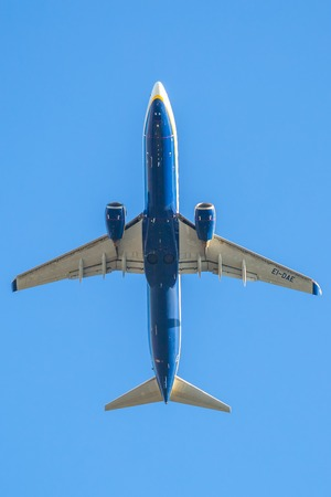 Bologna, Italy - December 20, 2016: low angle view of a Ryanair plane against sky, close up fling. blue Ryanair, low cost flights company, passenger airplane flight against blue background below view. Editorial