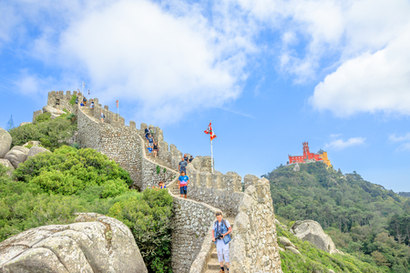 Sintra, Portugal - August 7, 2017: one of towers of panoramic Castle of the Moors with coloful Pena Palace in the distance. People visit one of the two most popular Sintra landmarks. Redakční