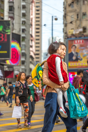 union familiar: Hong Kong, China - December 6, 2016: asian mother and a son in her arms at the Yee Wo Street junction on Hennessy Road downtown of Causeway Bay, one of the best travel destinations for tourists.