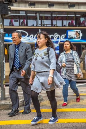 union familiar: Hong Kong, China - 6 de diciembre de 2016: Una familia asiática que se cruza el camino de Causeway Bay de la calle de Yee Wo, uno el centro de la ciudad más ocupado para las tiendas de la moda y del lujo, situadas en el camino de Henessy.