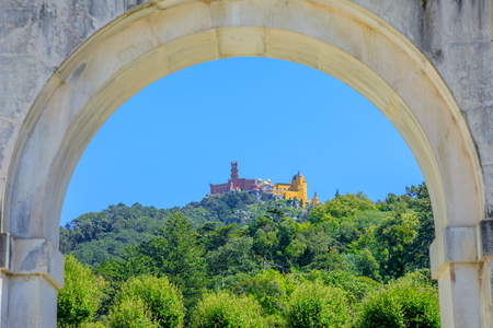 Close up of Pena National Palace in the blue sky surrounded by green hills, seen from the arch of Seteais Palace. Sintra historic center, Lisbon District, Portugal.