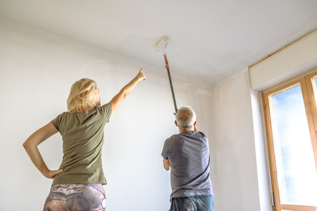 Housewife with painter at work showing the job painting a white ceiling with paint roller in empty room for renovation.
