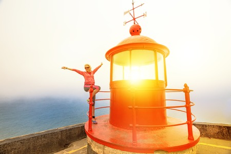 Happy caucasian woman with open arms sitting on red lighthouse or Farol da Nazare in Fortress of St. Michael. Female tourist at the popular viewpoint for surfing on giant waves in Nazare, Portugal. Banco de Imagens