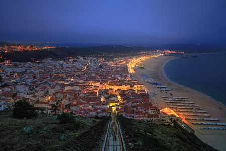 Panorama of Nazare in Portugal by night, the most popular seaside resorts in Silver Coast. Aerial view of skyline, beach and Ascensor da Nazare or Nazare Funicular from Nazare Sitio