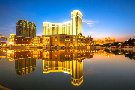Scenic panorama cityscape of Macau, China, reflected on lake at sunset. Urban night scene.