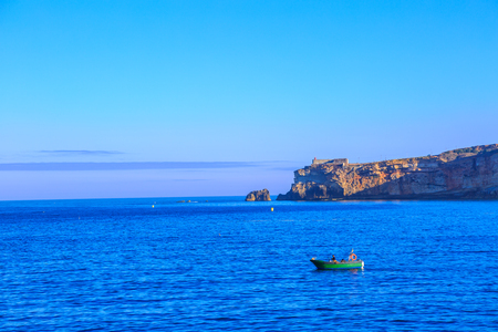 Traditional fishing boat sails in the calm waters in front of main beach of Nazare in Central Portugal. The high cliffs of Nazare with fortress and its lighthouse on background. Copy space. Stock Photo
