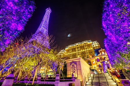 Macau, China - December 8, 2016: Christmas trees illuminated in front of The Parisian Macau Eiffel Tower, a luxury Resort Hotel Casino in Cotai Strip shines bright at night. Christmas holidays time.