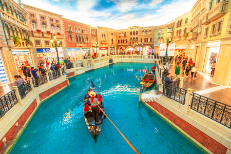 Macau, China - December 9, 2016: gondolier with tourists during a ride in an authentic gondola down Grand Canals at the Venetian Luxury Hotel and Casino. Inside shopping mall in Cotai Strip.