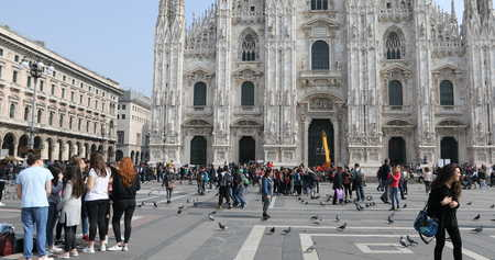 MILAN, ITALY- MARCH 7, 2017: Tourists walking and taking pictures with pigeons in Piazza Duomo of Milano fashion city. Ground view of this historic Gothic cathedral. Editorial