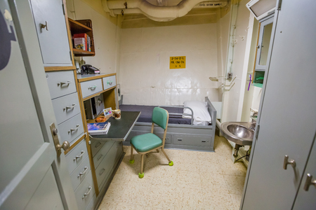 HONOLULU, OAHU, HAWAII, USA - AUGUST 21, 2016: small officer single room and personal office with washbasin, bed and teletypewriter of Battleship Missouri at Pearl Harbor, a military port in Oahu.