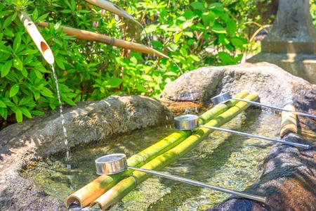 Schließen Sie oben vom japanischen Bambusbrunnen und von den Schöpflöffeln, die für das Waschen von Händen benutzt werden. Reinigungsbrunnen mit Schöpflöffeln an einem buddhistischen Tempel. Hase-dera in Kamakura, Japan. Japanische Kultur-Konzept. Standard-Bild - 92368317