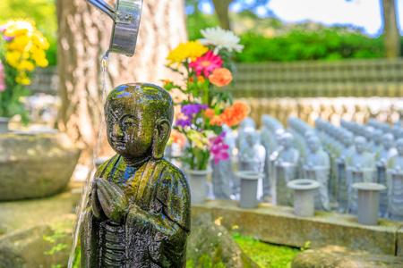 Anbetung bei Jizo Statue. Schöpflöffel gießt Wasser auf Jizos Kopf. Hase-deratempel in Kamakura, Japan. Japanische Kultur-Konzept. Standard-Bild - 92367709