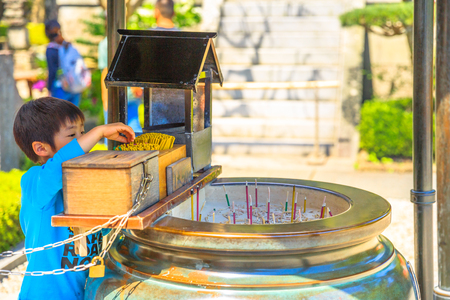 Kamakura, Japan - April 23, 2017: Japanese child lights up at incense stick burning inside giant bronze incense burner. Hase-dera Temple in Kanagawa Prefecture.Hasedera is popular landmark in Kamakura